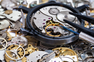 tools on open watch on pile of clock spare parts