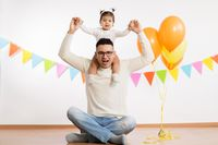 father and daughter with birthday party balloons
