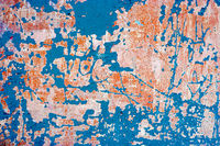 Abandoned wall with blue paint on. Grungy background with weathered plaster and destroied paint