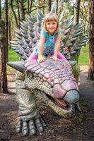 Cute little caucasian girl riding on Ankylosaurus dinosaur