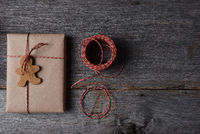 High angle shot of a Christmas Present with a Holiday Shaped Cookie, twine and copy space.