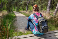 Female hiker with backpack sitting on forest path
