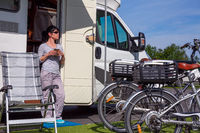 Woman is standing with a mug of coffee near the camper.
