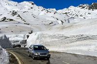 PKW fährt auf der Passtrasse zwischen hohen Schneemauern über den Gotthardpass