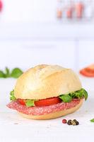 Brötchen Sandwich Baguette belegt mit Salami Schinken Hochformat Textfreiraum Copyspace auf Holzbrett