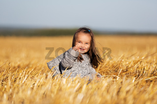 Happy two year old girl walking in a summer harvested field