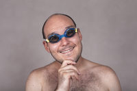 Funny man in swimming goggles daydreaming and looking at you