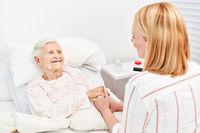 Frau tröstet bettlägerige Seniorin als Patient