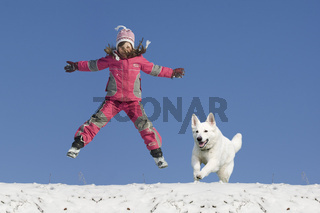 Mädchen springt im Schnee mit Hund, Girl jump in snow with dog
