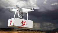 Unmanned Aircraft System (UAV) Quadcopter Drone Carrying Package With Biohazard Symbol Label Near Stormy Skies.