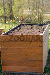 aufgestelltes Hochbeet mit Strauchschnitt und Erde befüllt