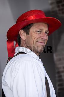 Portrait von Rene te Kulve, Mitglied der Käseträgergilde mit rotem Hut,Käsemarkt Alkmaar,Niederlande