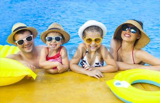 Happy family with two kids having fun in the swimming pool
