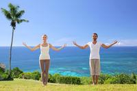 happy couple making yoga exercises on beach