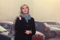 Fashion blond woman in black coat walking in a city street