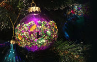 Encrusted with crystals Christmas tree decorations hang on a tre