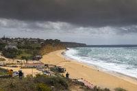 Main beach of Porto de Mos under dark clouds