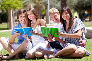 Smiling young couple holding books posing to camera