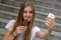 Young woman eating ice cream with smartphone