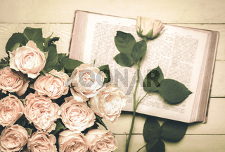 Roses bouquet and an open book in retro style