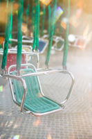 Green empty carousel seat at summer funfair