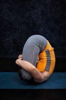Woman doing Hatha Yoga Ashtanga Vinyasa yoga asana Garbha pindas