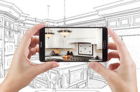Hands Holding Smart Phone Displaying Photo of Kitchen Drawing Behind