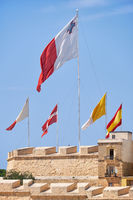 The flags flap over the fortress walls for a holiday. Malta