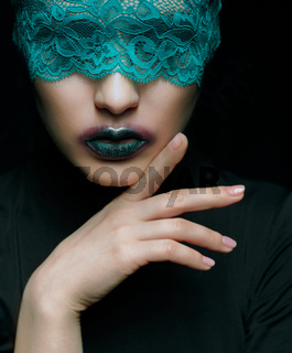 Halloween beauty portrait of young beautiful woman with green lacy ribbon on eyes