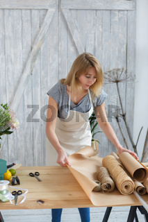 Young florist cutting paper wrapping