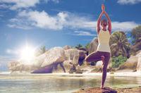 woman meditating in yoga tree pose over beach