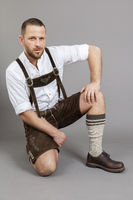 man in bavarian traditional lederhosen kneeling
