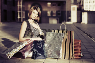 Young fashion woman with shopping bags sitting on the sidewalk
