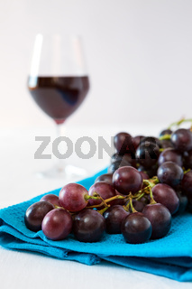 Closeup of a bunch of red grapes and a glass of red wine on background