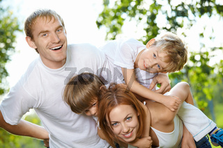 Young family from four members has fun in a summer garden