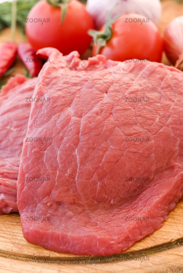 Raw beef fillet with vegetable as closeup on chopping bread