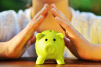 Protect your savings - with hands covering the green piggy bank