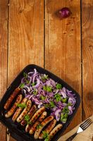 Fried sausages with onion and parsley in a pan on wooden background
