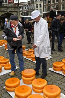 Bauer, links, und Käsehändler, rechts, feilschen um den Preis für Gouda Käse auf dem Käsemarkt,Gouda
