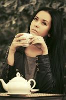 Young fashion woman in leather jacket drinking a tea at sidewalk cafe