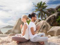 smiling couple making yoga exercises on beach