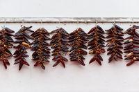 Strings of Espelette peppers drying