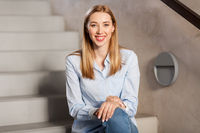 happy smiling woman or student sitting on stairs