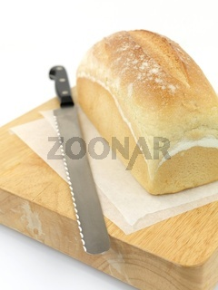 A loaf of bread on a cutting board isolated against a white background