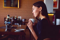 Young brunette with a coffee cup in a restaurant