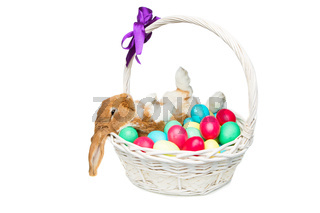 Beautiful domestic rabbit in basket with eggs