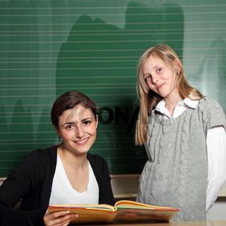 Nette Lehrerin mit Schulbuch und Schülerin vor der Tafel - quadratisch-