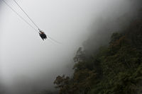 Tourists gliding on the zip line to a mountain against the background of the rain forest, Mindo, Ecuador