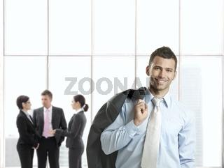 Happy businessman in office lobby