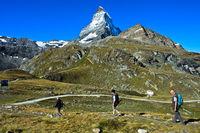 Three tourists in the hiking area around Zermatt, lake Schwarzsee and Matterhorn behind, Zermatt